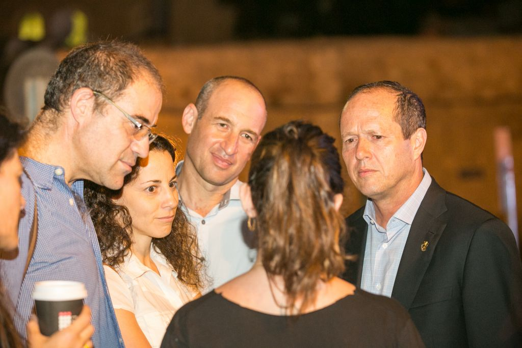 Jerusalem Mayor Nir Barkat, right, speaking to the parents of Shira Banki, who was murdered while marching in the 2015 Jerusalem Gay Pride Parade, at a memorial event in Jerusalem on July 19, 2016. (Noam Feiner/Yerushalmim)