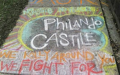 A chalk tribute to Philando Castile marked a sidewalk across the street from the Minnesota governor's residence as demonstrators gathered outside the residence Friday, July 8, 2016, in St. Paul, Minnesota, to protest the shooting death by police of Castile after a traffic stop Wednesday, July 6, in nearby Falcon Heights. (AP Photo/Jim Mone)