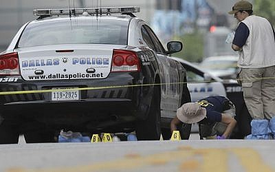 Investigators work in downtown Dallas on Saturday, July 9, 2016 in an area where five police officers were shot dead and seven others were injured by a gunman two days earlier. (AP Photo/Eric Gay)