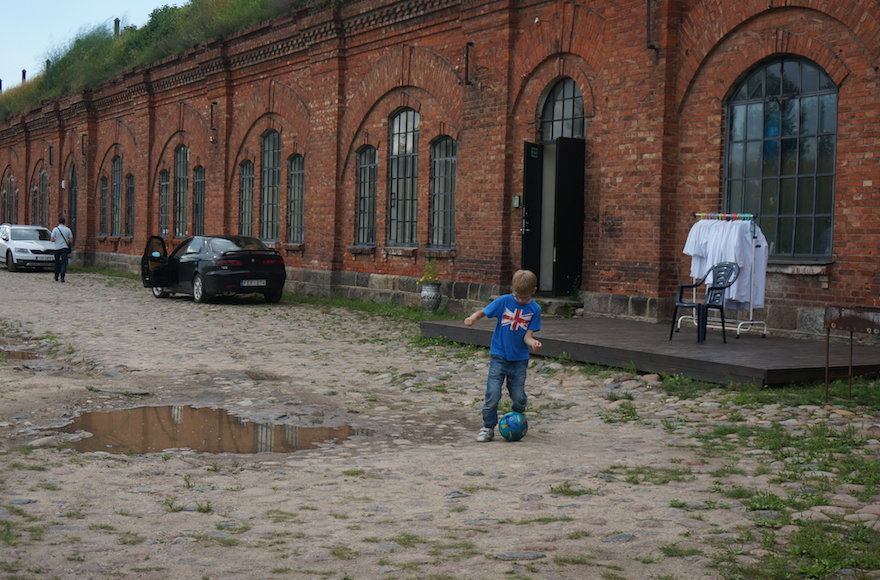 A boy playing soccer at the entrance to the former concentration camp known as the Seventh Fort in Kaunas, Lithuania, July 12, 2016. (Cnaan Liphshiz)