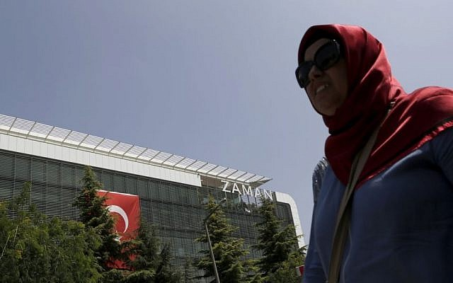 A woman walks past the headquarters of 'Zaman' newspaper, after being closed by the government in Istanbul, Thursday, July 28, 2016. (AP Photo/Petros Karadjias)