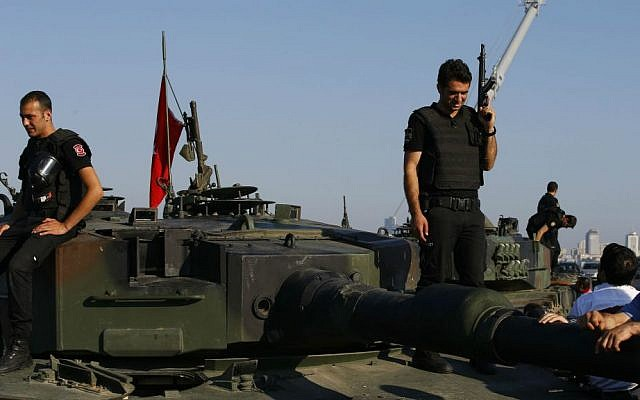 Turkish police officers, loyal to the government, stand atop tanks abandoned by Turkish army officers near Istanbul's iconic Bosporus Bridge, Saturday, July 16, 2016. (AP Photo/Emrah Gurel)