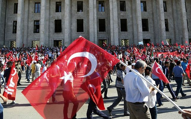 Turkish citizens wave their national flag as they protest against the military coup outside Turkey's parliament, near Turkish military headquarters in Ankara, Turkey, Saturday, July 16, 2016. (AP Photo/Hussein Malla)