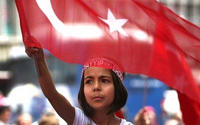 A Turkish girl wearing a headband bearing the name of Turkish president Recep Tayyip Erdogan during a pro-government demonstration in front of the old parliament building, in Ankara, Turkey, July 20, 2016. (AP Photo/Hussein Malla)