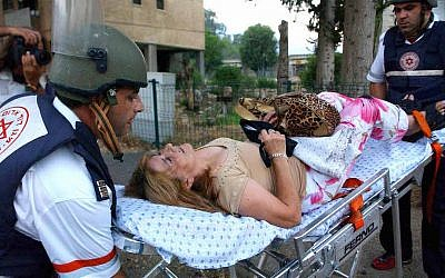Israeli medics evacuate a woman in shock from her home after a Hezbollah rocket attack in the northern Israeli town of Kiryat Shmona Thursday July 27, 2006.