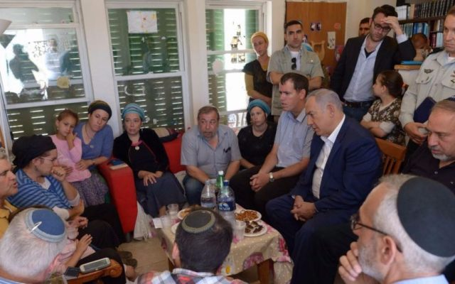 Prime Minister Benjamin Netanyahu (seated, second right) and Defense Minister Avigdor Liberman (seated, right) join mourners at the family home of slain teen Hallel Yaffa Ariel in Kiryat Arba on July 1, 2016, a day after she was murdered in her bed. (Amos Ben Gershom/GPO)