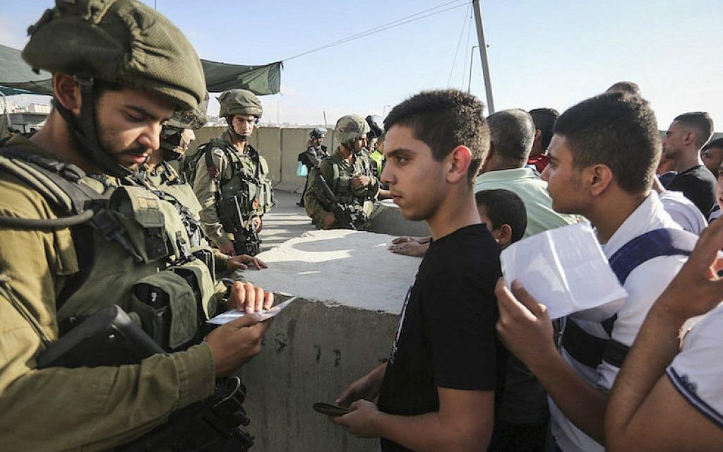 Israeli soldiers checking Palestinian IDs at the Qalandia checkpoint between the West Bank city of Ramallah and Jerusalem, July 1, 2016. (Flash90)
