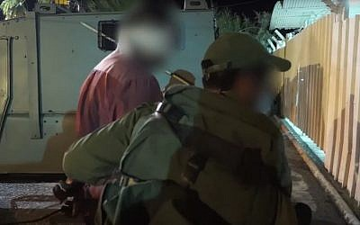 IDF troops detain a man during a July 27, 2016 raid in the West Bank to arrest a Hamas cell behind the murder of Rabbi Miki Mark (screen capture: YouTube)