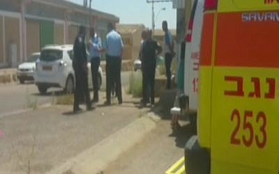 Police and paramedics around a car where a baby died after being left on July 12, 2016. (screen capture: Channel 2/MDA)