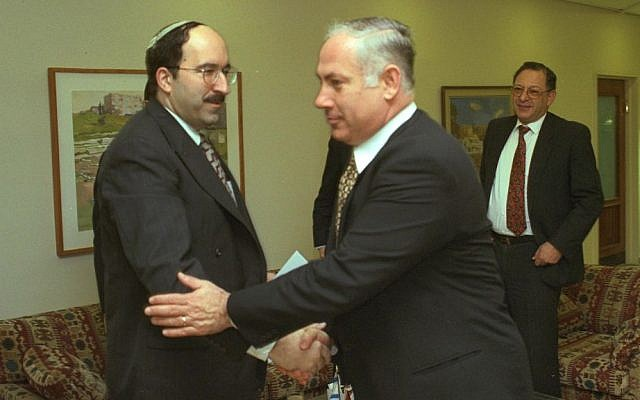 Prime Minister Benjamin Netanyahu, right, shakes hands with his policy advisor Dore Gold at the Prime Minister's Office in Jerusalem, January 1997 (Avi Ohayon/GPO)