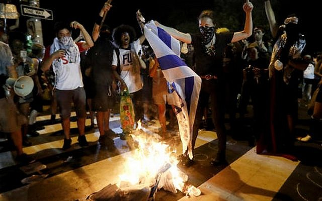Demonstrators burn a flag during a protest on the second day of the Democratic National Convention in Philadelphia on July 26, 2016. (AP Photo/John Minchillo)