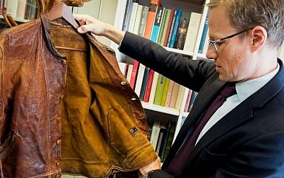Thomas Venning examines Albert Einstein's leather jacket ahead of an auction in which the clothing item will be sold. (Courtesy Christie's)