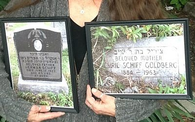 Danette Devlin holding photos of the gravestones of her great-grandparents Herman and Cyril Schiff, attesting to her Jewish roots. (Courtesy of Danette Devlin/via JTA)