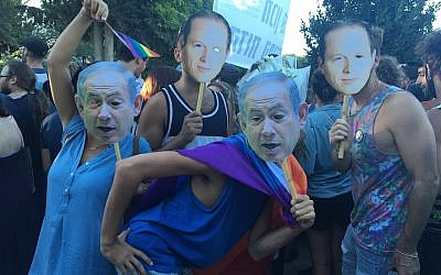 Liron Shimonie, far left, and Yuval Regev, center, wearing masks of Israeli Prime Minister Benjamin Netanyahu's face at the Jerusalem Pride Parade, July 21, 2016. (Andrew Tobin)