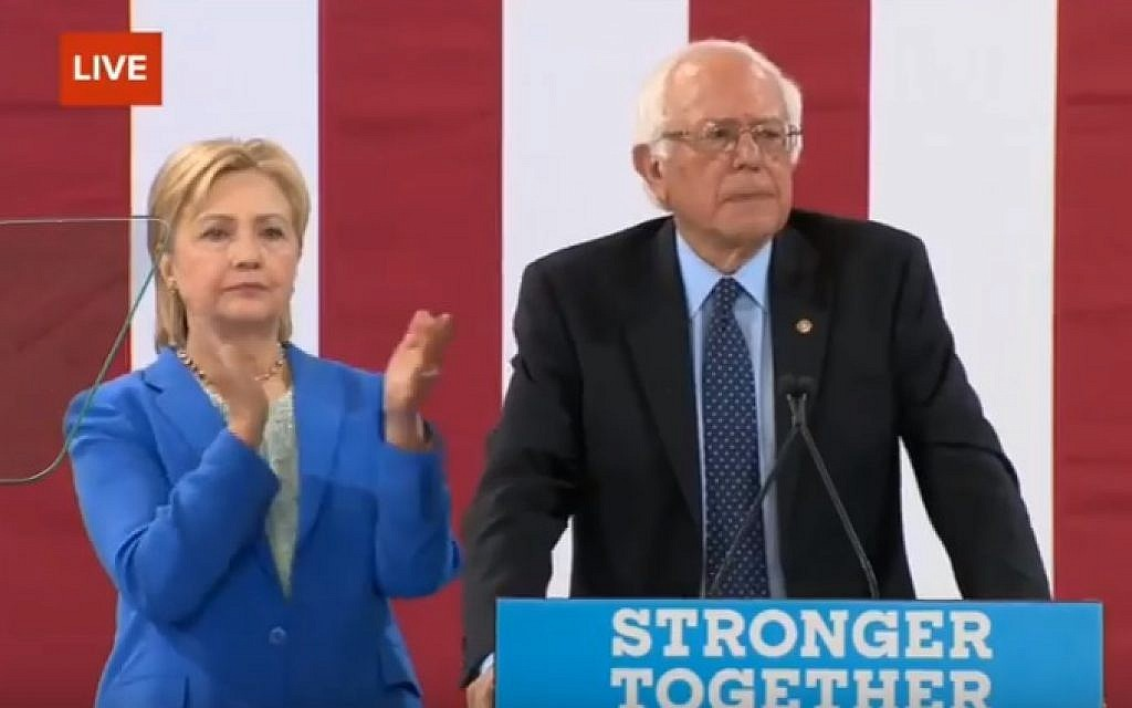 Hillary Clinton looks on as Bernie Sanders endorses her for US president, at a rally in New Hampshire on July 12, 2016 (screen capture: YouTube)