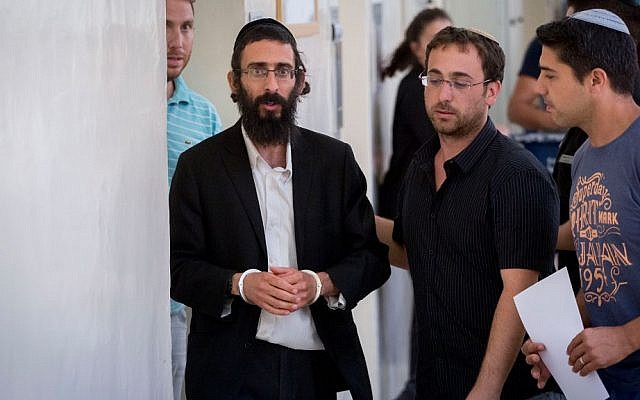 Michael Schlissel, brother of Yishai Schlissel, is led out of the courtroom at the Jerusalem Magistrate's Court on July 20, 2016. (Yonatan Sindel/Flash90)