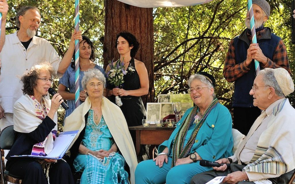 At 76, longtime activists Shoshana Dembitz, seated, center left, and Abigail Grafton, seated, center right, married in El Cerrito, Calif., on June 27. The ceremony was officiated by Rabbi Diane Elliot, seated left, and her husband, Rabbi Burt Jacobson. (Lea Delson via JTA)