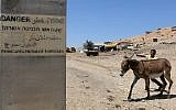 "A Palestinian boy walks a donkey on a road in the West Bank area of Tubas, on July 19, 2016, near a sign on a concrete block which reads in Hebrew, Arabic and English ""Firing area entrance forbidden."" (AFP PHOTO / JAAFAR ASHTIYEH)"