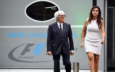 Formula One boss Bernie Eccleston and his wife, Fabiana Flosi in Singapore on September 18, 2014. (AFP PHOTO / TOSHIFUMI KITAMURA).