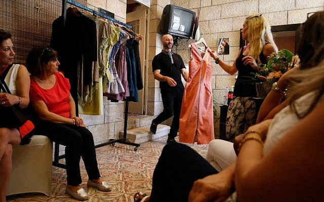 Palestinian American fashion designer Rami Kashou smiles as a Palestinian woman chooses one of his designs during a fitting session at a pop-up shop in the West Bank city of Ramallah on July 27, 2016. (Abbas Momani/AFP)