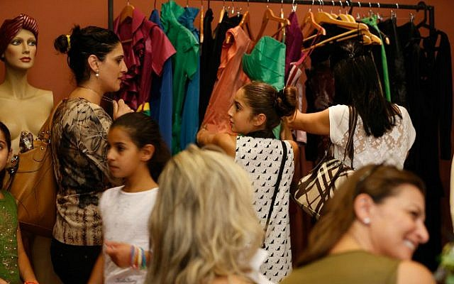 Palestinian women and their daughters choose dresses designed by Palestinian American fashion designer Rami Kashou during a fitting session at a pop-up shop in the West Bank city of Ramallah on July 27, 2016. (Abbas Momani/AFP)