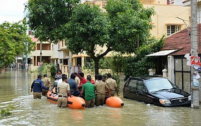 Members of the fire forces and volunteers participate in relief operations in a low-lying flooded area of Bangalore, India, July 29, 2016. (AFP/MANJUNATH KIRAN)
