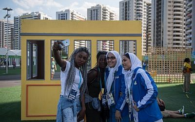 Members of Iran's Olympic team pose for selfies with two performers prior to a welcoming ceremony held at the athletes village of the Rio 2016 Olympic Games on August 1, 2016. / AFP PHOTO / Ed JONES