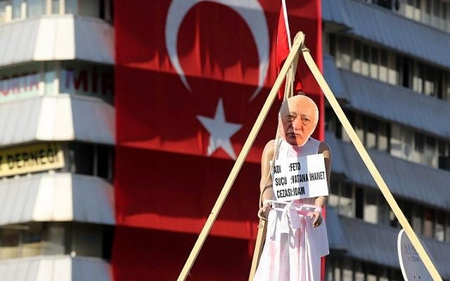 A picture of US-based preacher Fethullah Gulen placed on a hanging dummy in front of a Turkish national flag at Kizilay Square in Ankara on August 2, 2016, during a protest against July's failed military coup. (AFP Photo/Adem Altan)