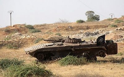 A tank bearing an Islamist flag is seen in a field as a Syrian coalition of jihadists and Islamist rebels seized key positions south of Aleppo in a major offensive to break the government siege of the city, on August 6, 2016, the Syrian Observatory for Human Rights said. (AFP/Omar haj Kadour)