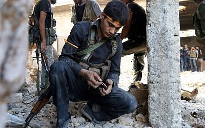 A rebel fighter reloads the magazine of his weapon during clashes with regime forces  in Ramussa on the southwestern edges of Syria's northern city of Aleppo on August 6, 2016. (AFP PHOTO/FADI AL-HALABI)