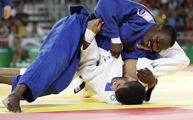 Israel's Golan Pollack (in white) competes with Zambia's Mathews Punza during their men's -66kg judo contest match of the Rio 2016 Olympic Games in Rio de Janeiro on August 7, 2016. (AFP/Jack GUEZ)