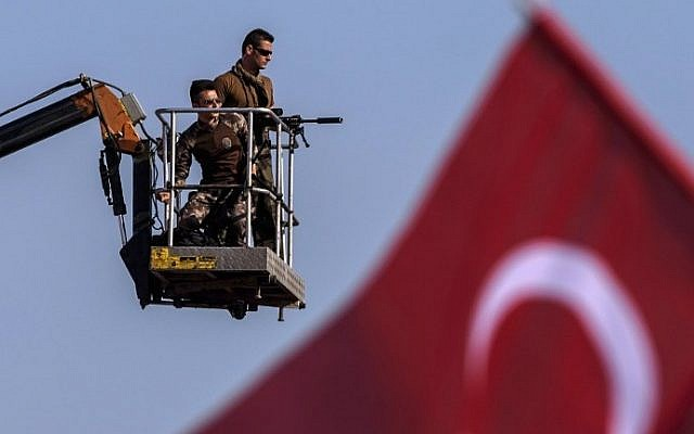 Turkish special force police officers stand guard as people wave Turkish national flags during a rally against failed military coup, in Istanbul, August 7, 2016. (AFP/OZAN KOSE)