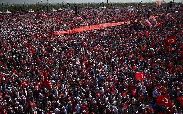 File: Demonstrators wave Turkish national flags and hold a giant banner with Turkish national flags as they stand in front of giant screens next to balloons in the color of the Turkish national flag during a rally against failed military coup, in Istanbul, August 7, 2016. (AFP/BULENT KILIC)