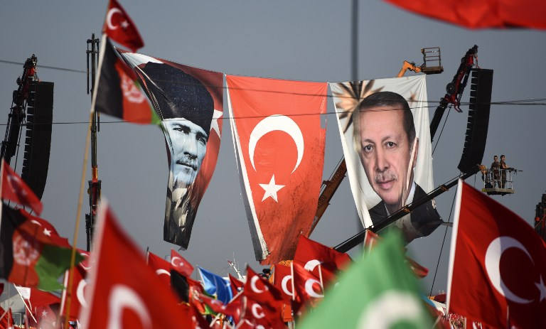 Turkish special force police officers stand guard next to a banner picturing Mustafa Kemal Ataturk, right, and Turkish President Recep Tayyip Erdogan as people wave Turkish national flags during a rally against failed military coup, in Istanbul, August 7, 2016. (AFP/BULENT KILIC)