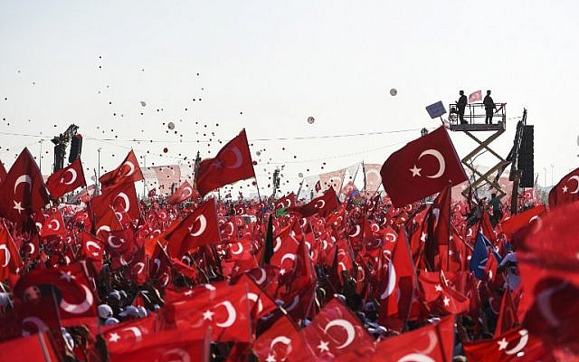 Demonstrators wave Turkish national flags as they stand in front of giant screens and Turkish special force police officers standing guard during a rally against failed military coup, in Istanbul, August 7, 2016. (AFP/BULENT KILIC)