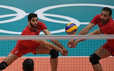 Iran's Milad Ebadipour Ghara H. (L) and Hamzeh Zarini go to dig the ball during the men's qualifying volleyball match between the Argentina and Iran at the Maracanazinho stadium in Rio de Janeiro on August 7, 2016, during the Rio 2016 Olympic Games (AFP PHOTO / PEDRO UGARTE)
