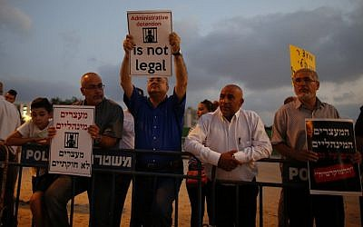 Illustrative: Arab MK Ahmad Tibi (C) holds a poster against administrative detention during a demonstration in support of Palestinian prisoner Bilal Kayed (portrait), who has been fasting for 53 days over his detention without trial, as they demonstrate outside the Ashkelon hospital where he is being held on August 9, 2016. (AFP Photo/Ahmad Gharabli)