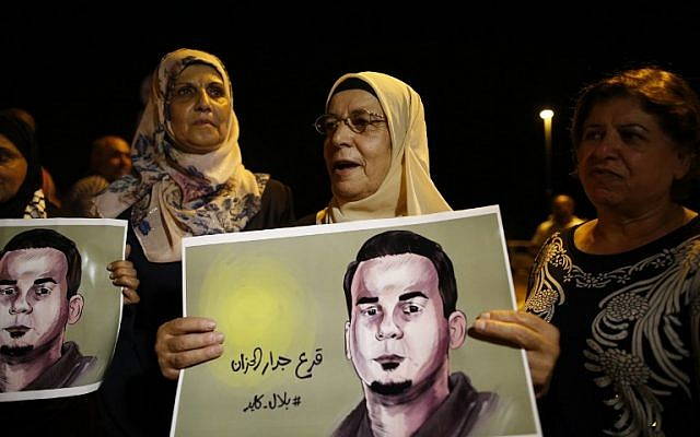 The mother (C) of Palestinian prisoner Bilal Kayed (portrait), who has been fasting for 53 days over his detention without trial, demonstrates against administrative detention and in support of her son outside the Ashkelon hospital where he is being held due to medical reasons including kidney failure and a severe loss of weight on August 9, 2016. (AFP PHOTO / AHMAD GHARABLI)