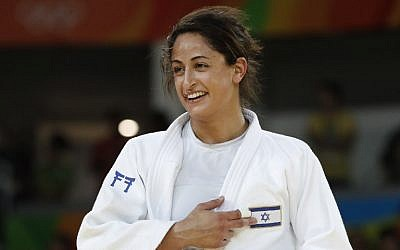 Israel's Yarden Gerbi points to the Israeli flag, after defeating Japan's Miku Tashiro to win the bronze medal in the women's under-63kg judo contest, at the Rio 2016 Olympic Games on August 9, 2016. (AFP Photo/Jack Guez)