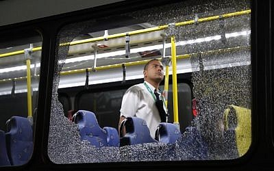 The damages to the windows of an Olympic bus hit while driving on the Transolympica Highway are inspected by an official in Rio de Janeiro on August 9, 2016. (AFP PHOTO / LA NACION / Maximiliano AMENA)
