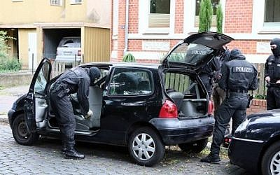 Police inspectors search a car on August 10, 2016 in Hildesheim, Germany. (AFP PHOTO / dpa / Christian Gossmann)