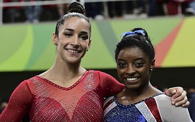 US gymnast Simone Biles (R) and  her compatriot Alexandra Raisman celebrate after the women's individual all-around final of the Artistic Gymnastics at the Olympic Arena during the Rio 2016 Olympic Games in Rio de Janeiro on August 11, 2016. (AFP PHOTO / Emmanuel DUNAND)