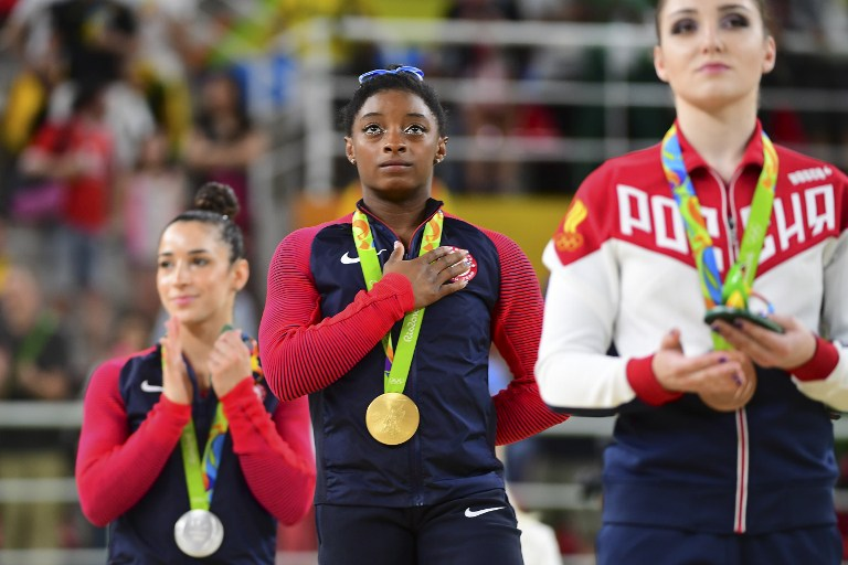 (R-L) Russia's Aliya Mustafina, US gymnasts Simone Biles and Alexandra Raisman on the podium of the women's individual all-around final of the Artistic Gymnastics at the Olympic Arena during the Rio 2016 Olympic Games in Rio de Janeiro on August 11, 2016. Biles won the event ahead of her compatiot Raisman and Mustafina. (AFP PHOTO / EMMANUEL DUNAND)