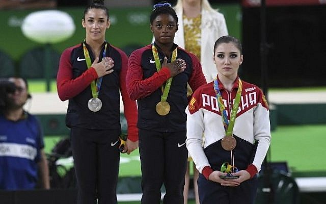 Russia's Aliya Mustafina (right), and Americans Simone Biles (center) and Alexandra Raisman (left) on the podium of the women's individual all-around final of the Artistic Gymnastics during the Olympic Games in Rio de Janeiro, Brazil, on August 11, 2016. (AFP/Ben Stansall)