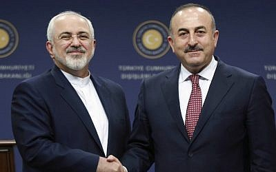 Turkish Foreign Minister Mevlut Cavusoglu, right, and Iran's Foreign Minister Mohammad Javad Zarif shake hands following a joint press conference at the Foreign Ministry in Ankara on August 12, 2016. (AFP/Adem Altan)
