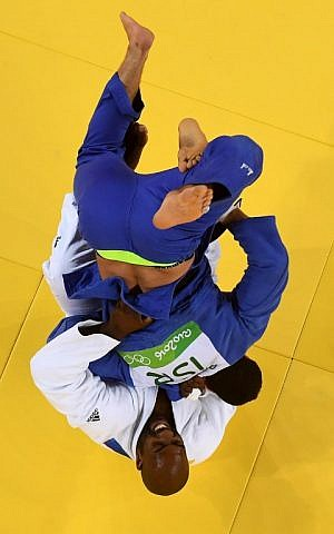 France's Teddy Riner (white) competes with Israel's Or Sasson during their men's +100kg judo contest semifinal A match of the Rio 2016 Olympic Games in Rio de Janeiro on August 12, 2016. (AFP PHOTO/Laurent KALFALA)