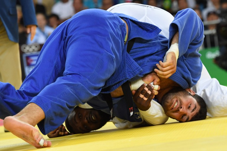 Cuba's Alex Garcia Mendoza (white) competes with Israel's Or Sasson during their men's +100kg judo contest bronze medal B match of the Rio 2016 Olympic Games in Rio de Janeiro on August 12, 2016. (AFP PHOTO/Toshifumi KITAMURA)
