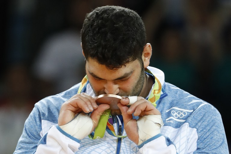 Or Sasson kisses his bronze medal on the podium in Rio de Janeiro on August 12, 2016. (AFP/Jack Guez)
