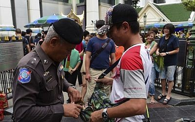 File: A Thai policeman searches a visitor's bag in the center of Bangkok, Thailand, August 13, 2016. (AFP/Munir Uz Zaman)