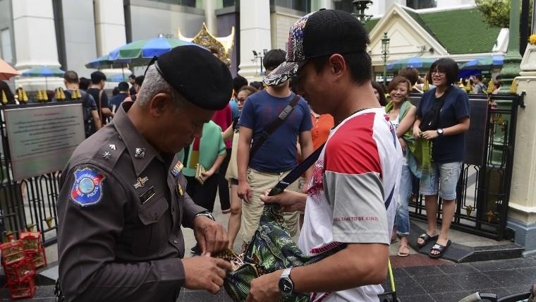 4b41cd5e0 File: A Thai policeman searches a visitor's bag in the center of Bangkok,  Thailand
